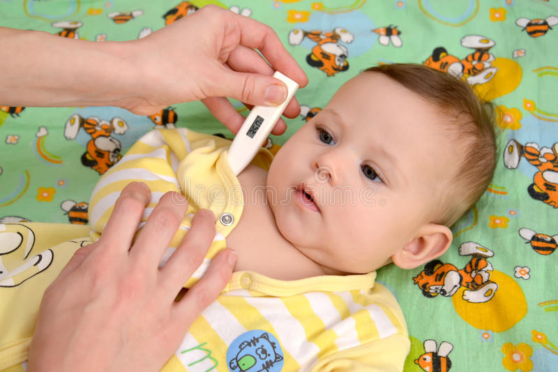 Kvinnan tar temperatur till det sjukt behandla som ett barn den elektroniska termometern royaltyfria foton