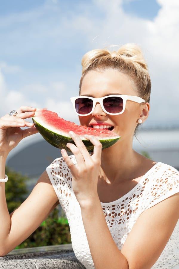 Kvinnan tar vattenmelon. Begrepp av sund och banta mat arkivbild