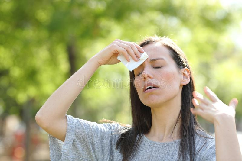 Kvinnan torka att använda för svett torkar i en varm sommardag arkivbild