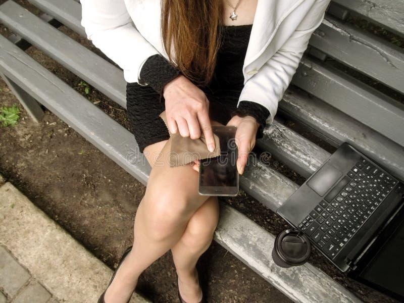 Kvinnan torkar skärmen av mobilen med ett stycke av torkduken Partisk bästa sikt av den kvinnliga kroppen, en bärbar dator och et royaltyfri foto