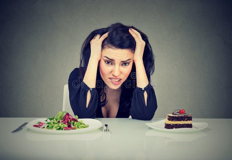 Kvinnan tröttade av bantar begränsningar som avgör att äta sund mat eller kakan som hon kräver fotografering för bildbyråer