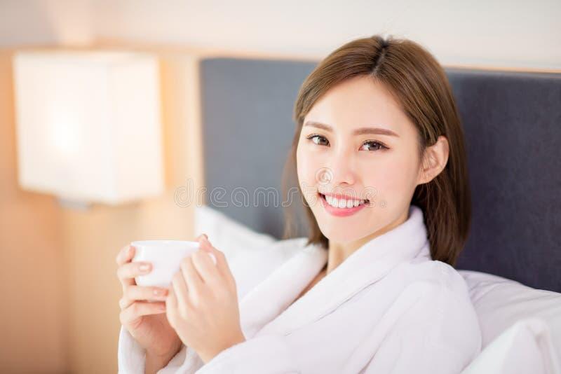 Kvinnan tycker om kaffe i morgon royaltyfria bilder