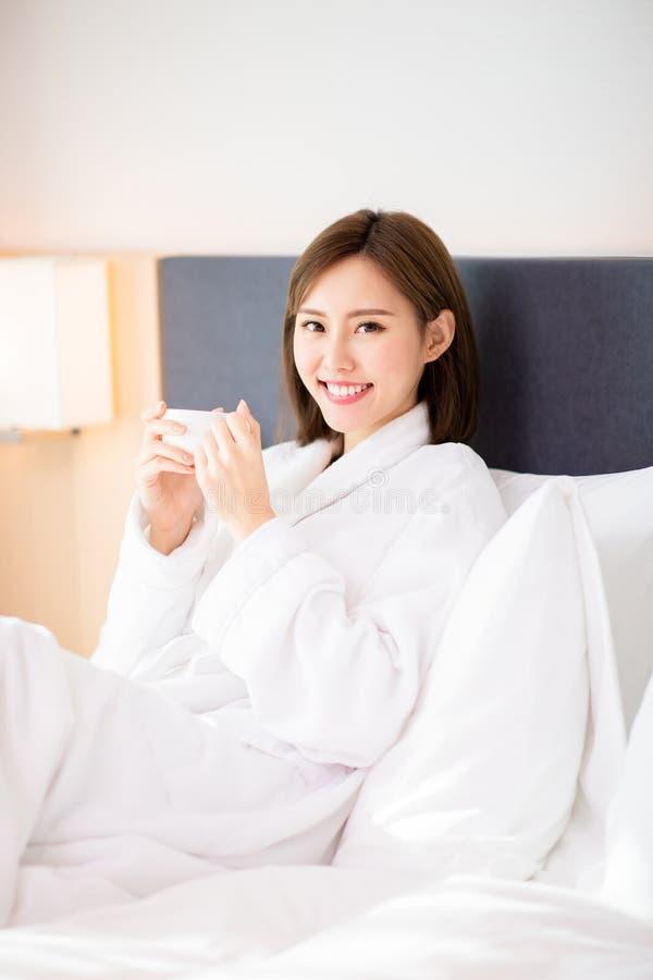 Kvinnan tycker om kaffe i morgon arkivbilder