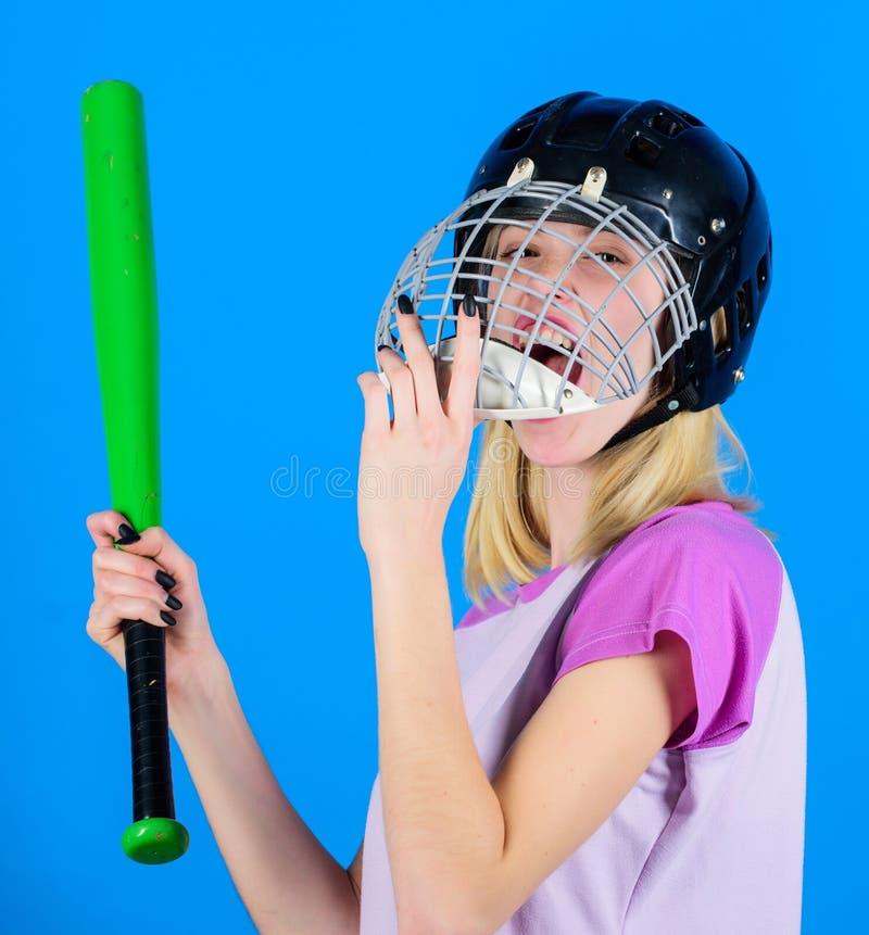 Kvinnan tycker om lekbasketmatchen För kläderbaseball för flicka säkert nätt blont hjälm och hållslagträ på blå bakgrund Kvinna royaltyfria foton