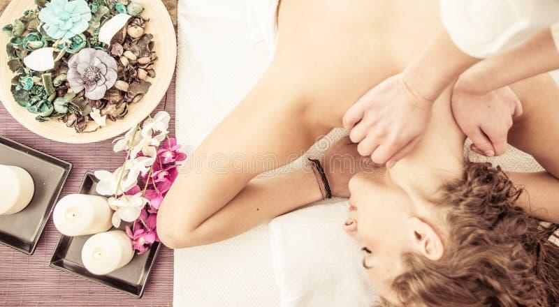 Kvinnan tycker om massage i brunnsortsalongen royaltyfria foton