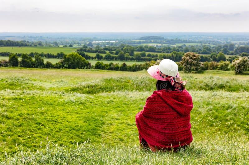 Kvinnan tycker om sikt av lantgårdländer, medan sitta ner i fält royaltyfri bild