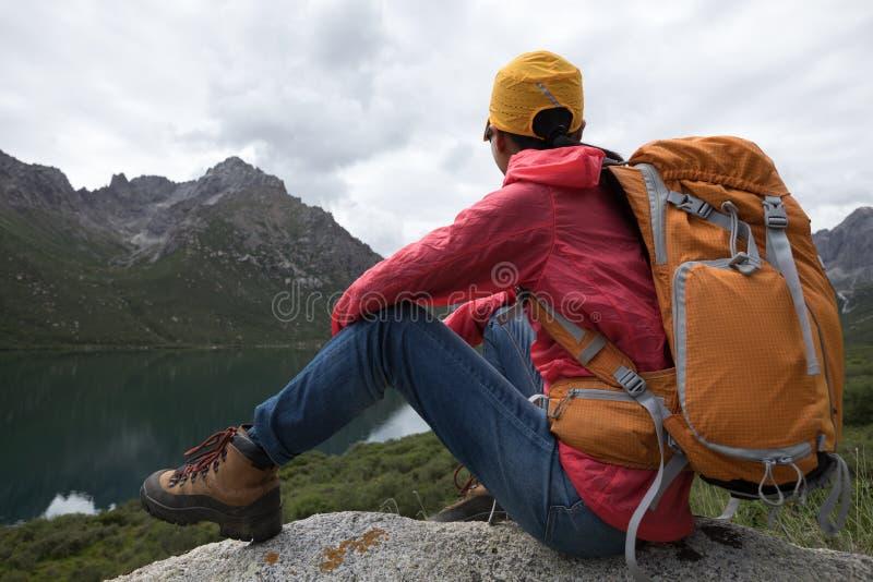 Kvinnan tycker om sikten sitter på lakeside vaggar arkivbilder