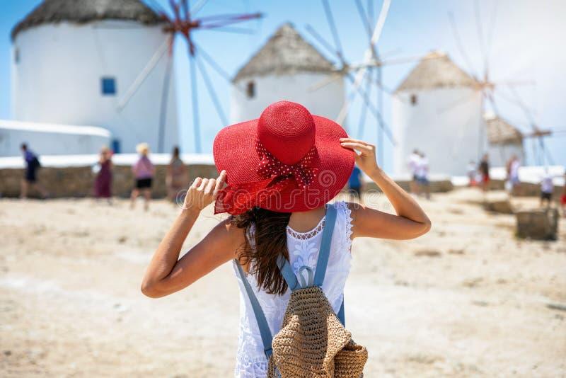 Kvinnan tycker om sikten till de berömda väderkvarnarna i den Mykonos ön, Cyclades, Grekland royaltyfri bild