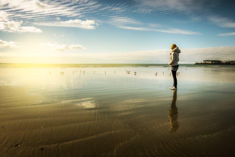 Kvinnan tycker om solnedgång på stranden arkivfoton