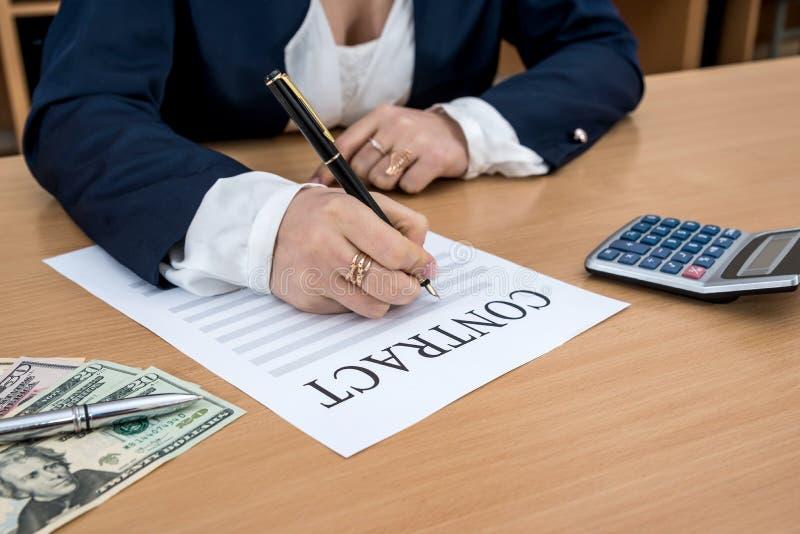 Kvinnan undertecknar avtalet dollar, räknemaskin och penna arkivfoton