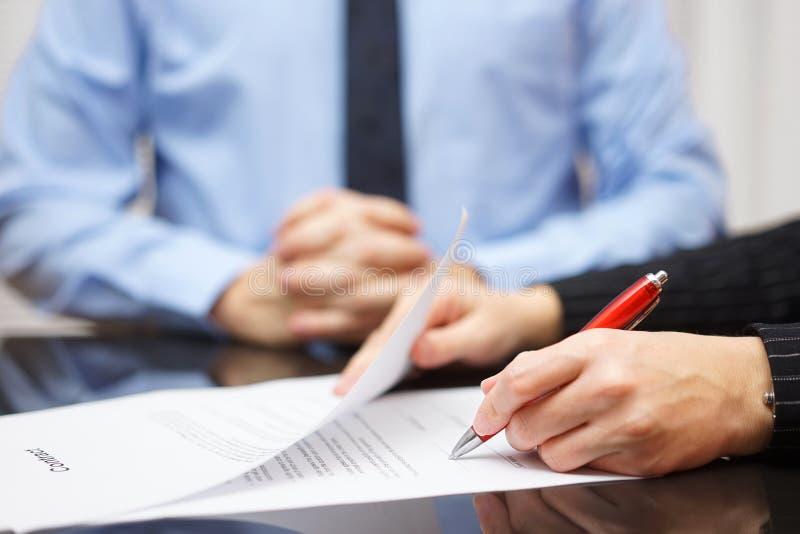 Kvinnan undertecknar avtalet med affärsmannen i bakgrund arkivfoton