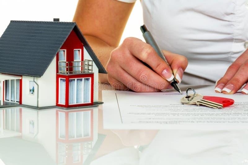 Kvinnan undertecknar köpöverenskommelse för hus arkivbild