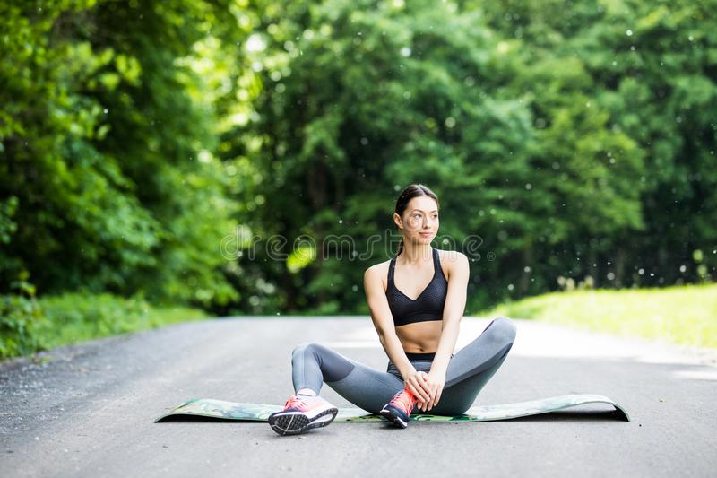 Kvinnan utför sträckning för sport i som ska parkeras utomhus royaltyfria bilder