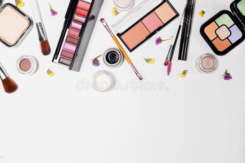 Kvinnan utgör produkter och tillbehör på vit bakgrund yrkesmässiga dekorativa skönhetsmedel, makeuphjälpmedel royaltyfri foto