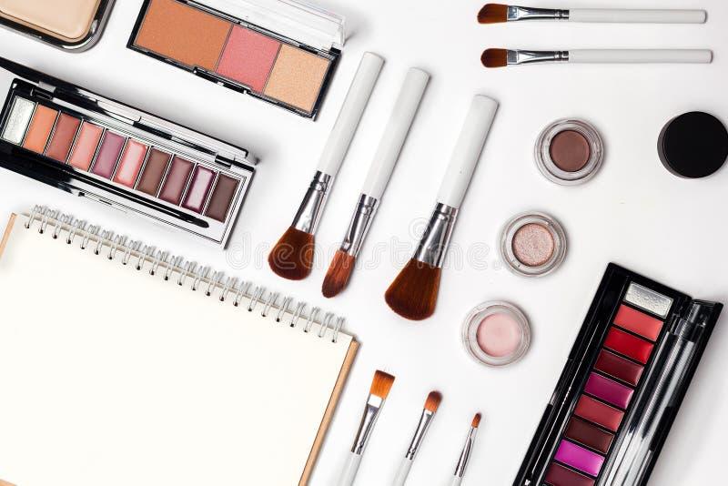 Kvinnan utgör produkter och tillbehör på vit bakgrund yrkesmässiga dekorativa skönhetsmedel, makeuphjälpmedel arkivbilder
