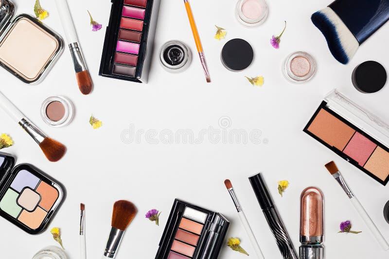 Kvinnan utgör produkter och tillbehör på vit bakgrund yrkesmässiga dekorativa skönhetsmedel, makeuphjälpmedel arkivfoto