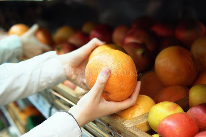 Kvinnan väljer grapefrukten i supermarket royaltyfri fotografi