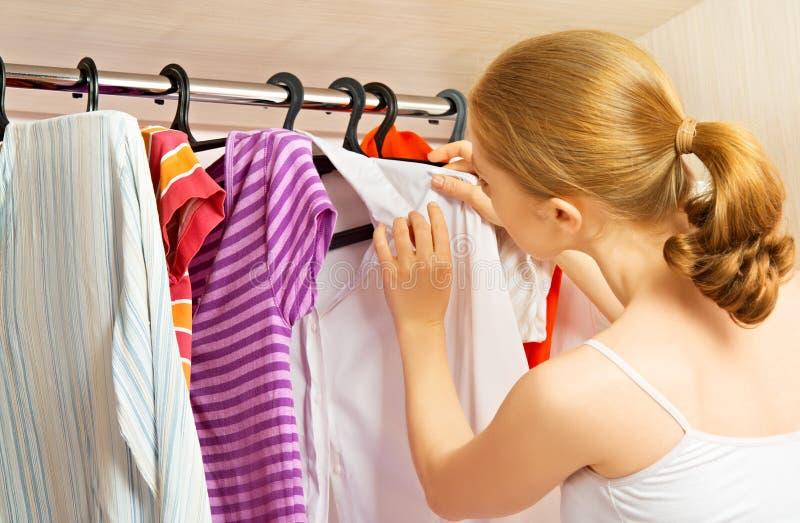 Kvinnan väljer kläder i garderobgarderoben hemma royaltyfria foton