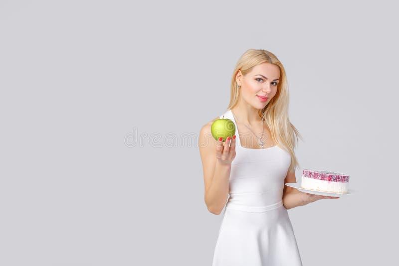 Kvinnan väljer mellan kakan och äpplet royaltyfri bild