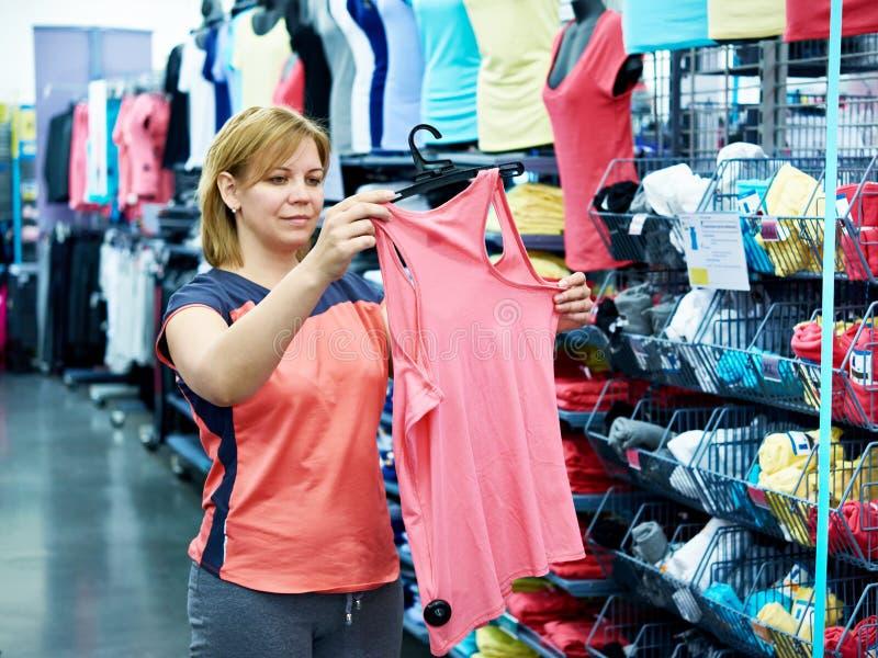 Kvinnan väljer sportwearen för kondition fotografering för bildbyråer