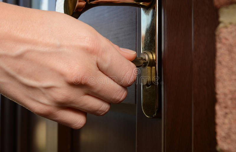 Kvinnan vänder tangenten i ett lås på en yttre dörr royaltyfri fotografi