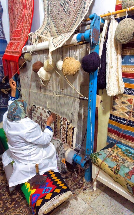 Kvinnan väver en traditionell matta vid handen i Kairouan, Tunisien royaltyfria bilder