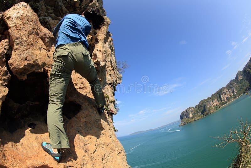 Kvinnan vaggar klättrareklättring på sjösidabergklippan arkivfoto