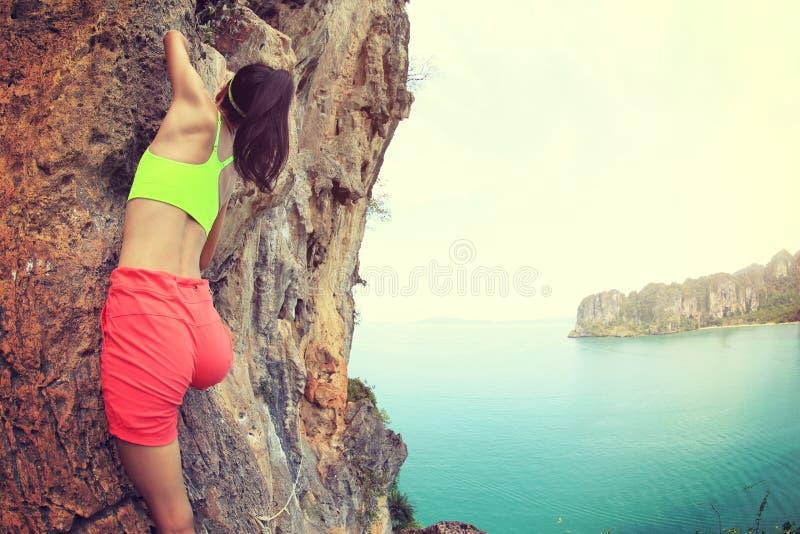 Kvinnan vaggar klättraren som klättringen på sjösidaberget vaggar royaltyfri bild