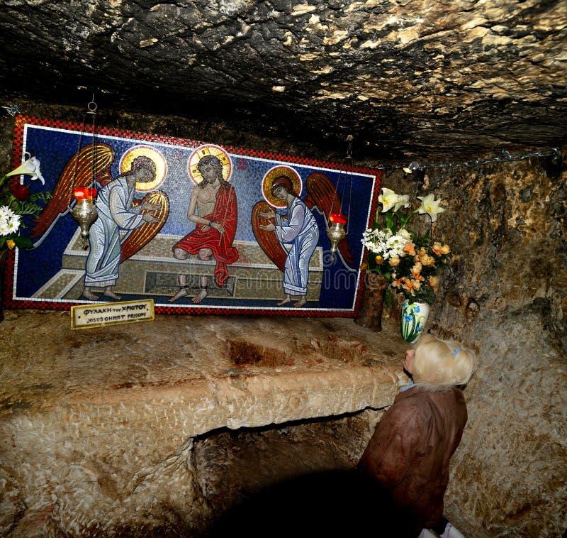 Kvinnan vallfärdar ber i fängelse av Jesus Christ royaltyfri bild