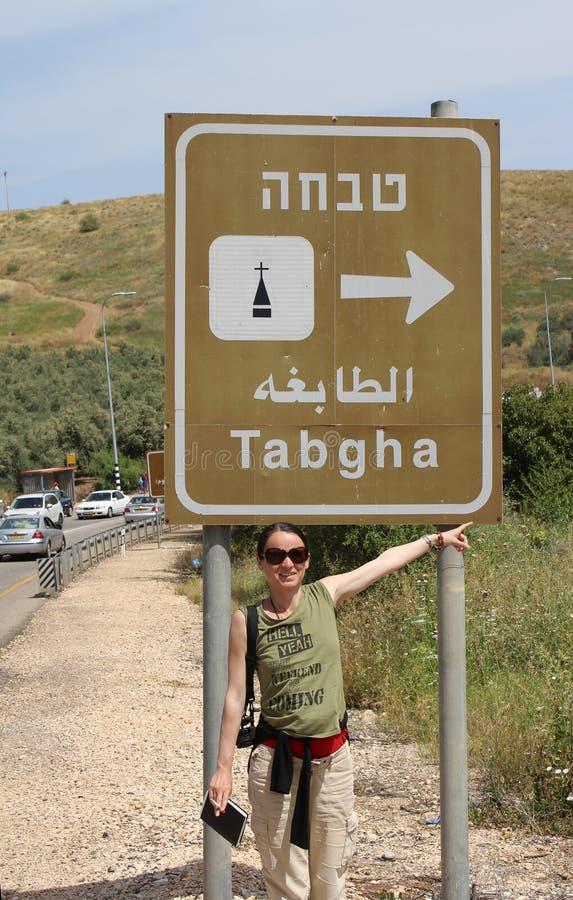 Kvinnan vallfärdar ovanför det Tabgha tecknet På vägen till kyrkan av multiplikation av loaves och fisken i Tabgha Israel pilgrim royaltyfria foton