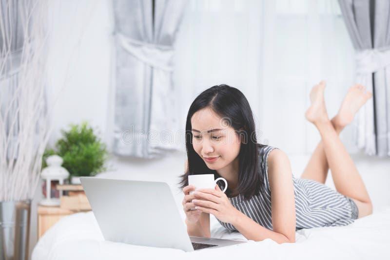 Kvinnan vilar och koppla av på säng genom att använda bärbar datordatoren arkivfoton