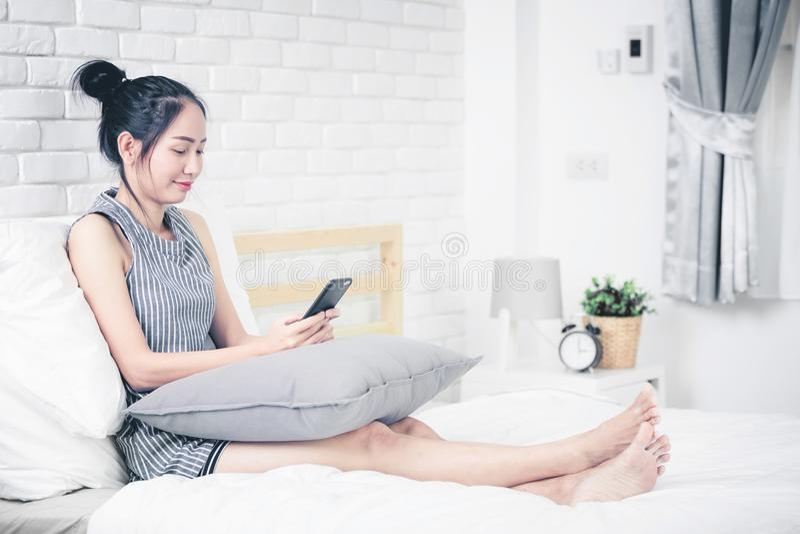 Kvinnan vilar och koppla av på säng genom att använda mobiltelefonapparater arkivbilder