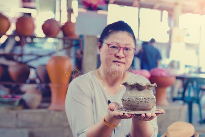 Kvinnan visar arbetet av krukmakeristöpningen arkivbild