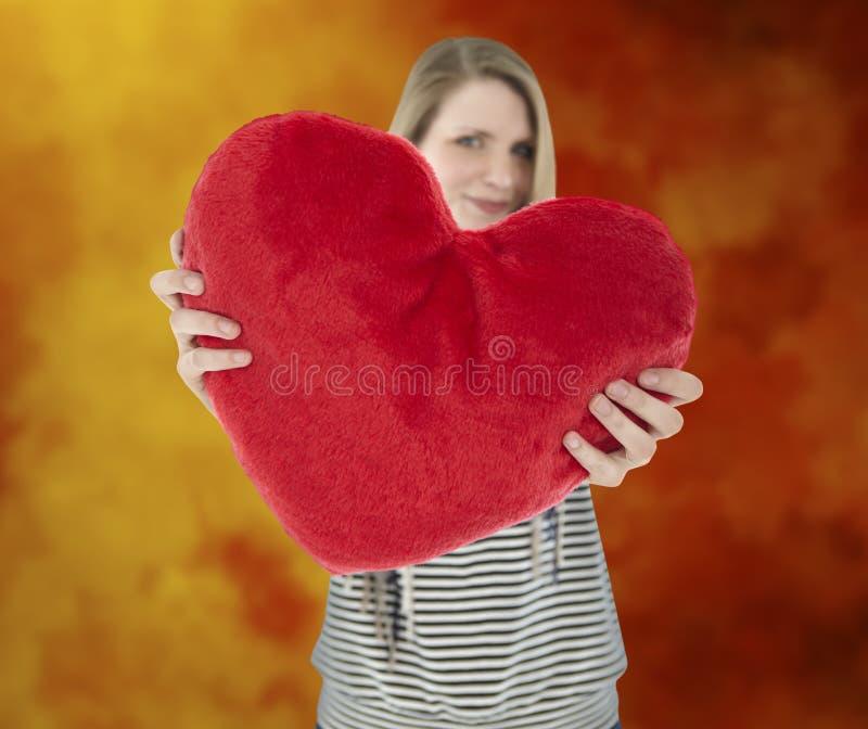 Kvinnan visar hjärtakudden fotografering för bildbyråer