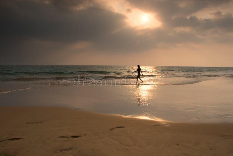 Kvinnan wallking på den Hikkaduwa stranden, Sri Lanka arkivbilder