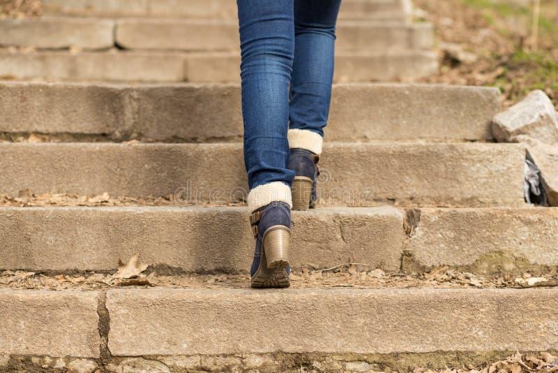 Kvinnans ben i vinter startar att kliva på trappa fotografering för bildbyråer