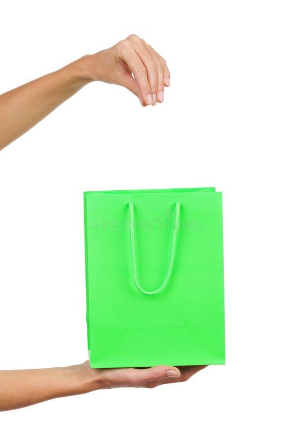 Kvinnans hand drar ut något från grön shoppingpåse royaltyfri bild