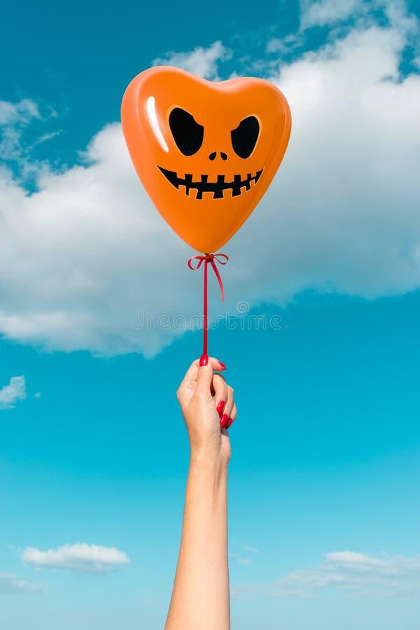Kvinnans hand med allhelgonaaftonframsidan på hjärtan formade ballongen på bakgrund av himmel arkivfoton