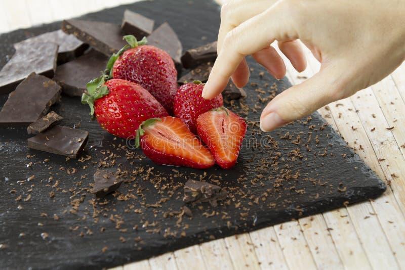 Kvinnans hand omkring som tar en av de trevligt förlade jordgubbarna på, kritiserar plattan med huggen av choklad och grated omkr royaltyfri foto