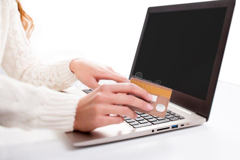 Kvinnans hand skriver in data genom att använda bärbar dator- och innehavkreditkorten in royaltyfri bild