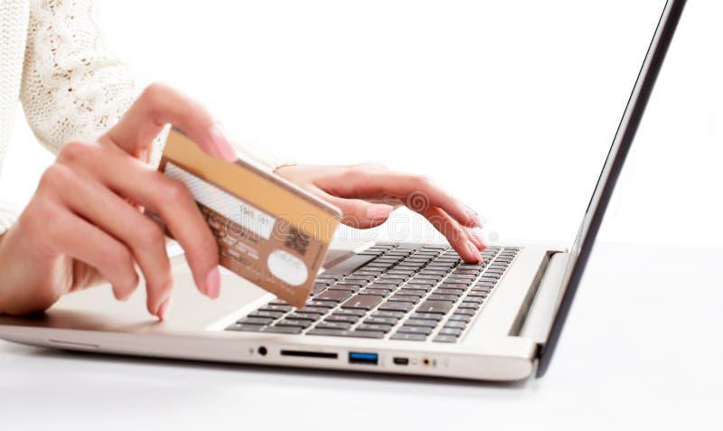Kvinnans hand skriver in data genom att använda bärbar dator- och innehavkreditkorten in arkivbilder