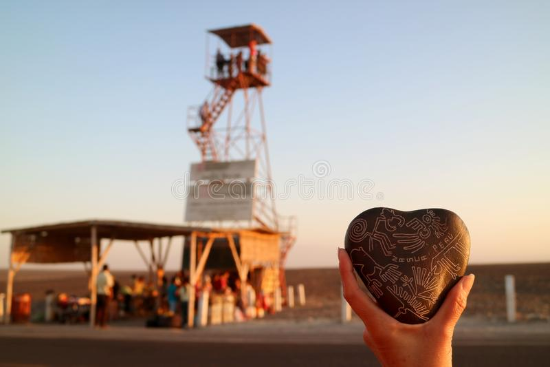 Kvinnans hand som rymmer en souvenir av Nazca linjer, sned den hjärta formade stenen mot oskarpt observationstorn av Nazca, Peru arkivfoton