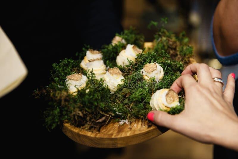 Kvinnans hand tar ett stycke av en exotisk maträtt under en lyxig företags händelsematställe royaltyfria bilder