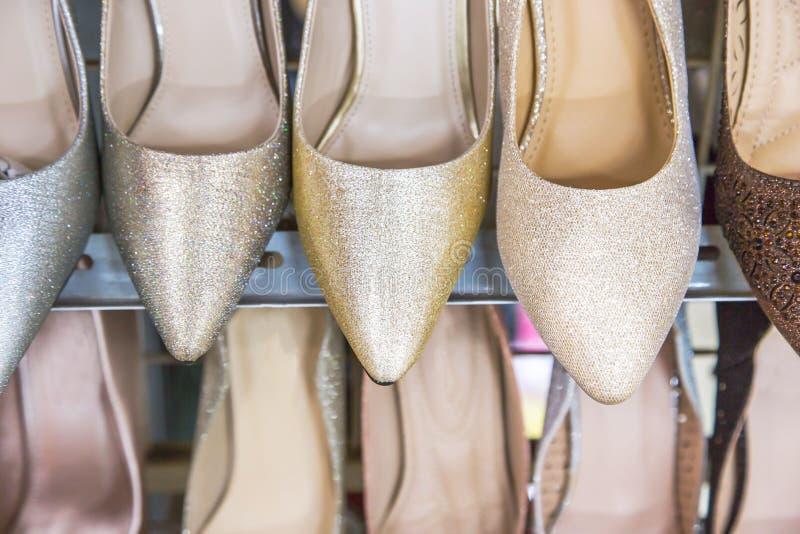 Kvinnans shoppar klassiska skor på hyllorna av skon royaltyfri fotografi