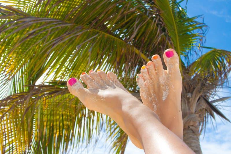 Kvinnans skönhet lägger benen på ryggen med modepedikyr på stranden royaltyfria foton