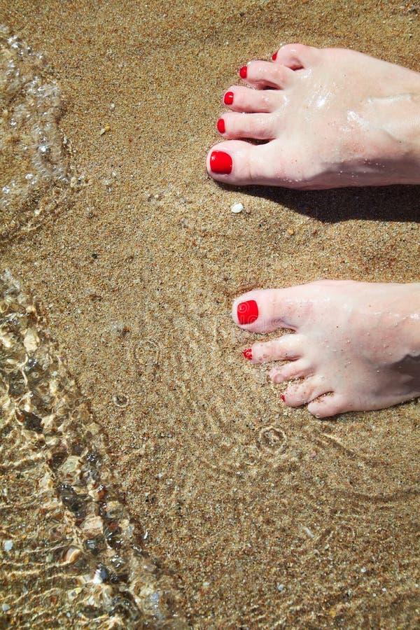 Kvinnans spikar pedicured fot med rött polermedel på tår i sanden i vatten arkivfoto