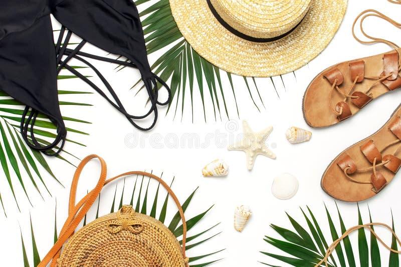 Kvinnans strandtillbehören lägger framlänges Tropiska palmblad för runda moderiktiga för rottingpåsesugrör för hatt för svart för royaltyfria foton