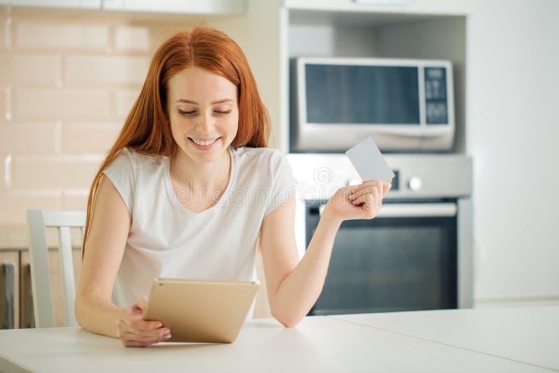 Kvinnaonline-shopping genom att använda minnestavlan och kreditkorten i kök royaltyfri fotografi