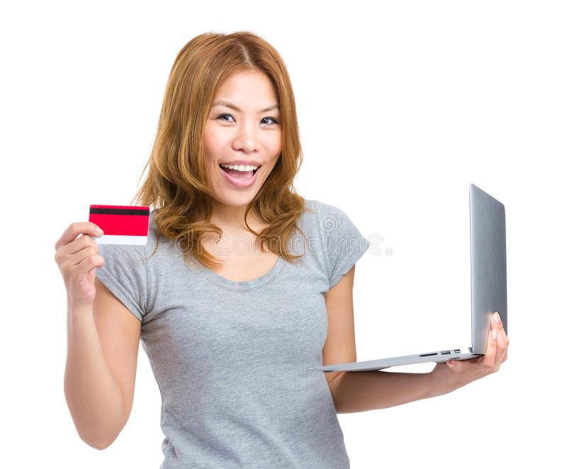 Kvinnaonline-shopping med att använda den bärbar datordatoren och kreditkorten arkivbild
