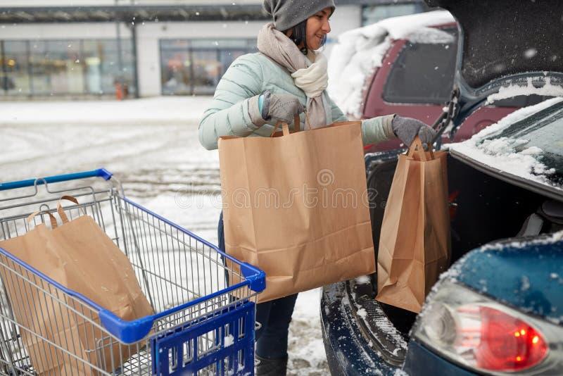 Kvinnapäfyllningsmat från shoppingvagnen till bilstammen royaltyfria bilder